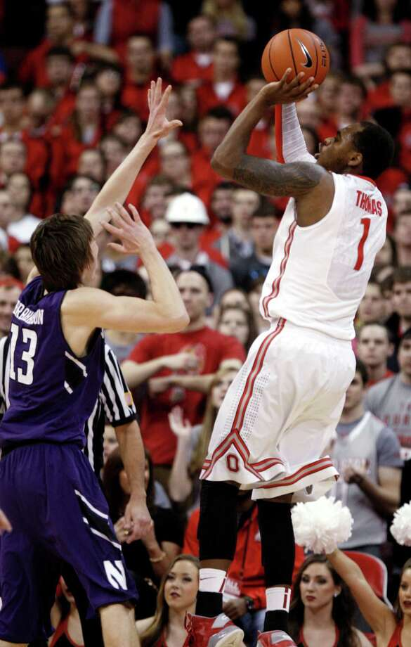 Ohio State's Deshaun Thomas, right, goes up for a shot against Northwestern's Kale Abrahamson during the first half of an NCAA college basketball game in Columbus, Ohio, Thursday, Feb. 14, 2013. Ohio State won 69-59. (AP Photo/Paul Vernon) Photo: Paul Vernon