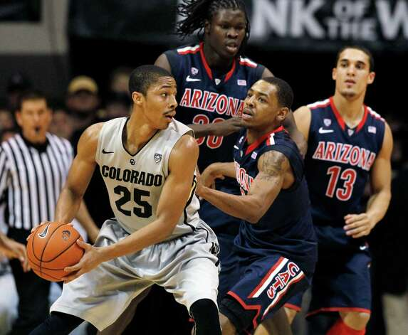 Colorado guard Spencer Dinwiddie (25) looks to pass the ball under pressure from Arizona guard Mark Lyons, front right, as forward Angelo Chol, rear left, and guard Nick Johnson cover in the second half of their NCAA college basketball game in Boulder, Colo., Thursday, Feb. 14, 2013. (AP Photo/David Zalubowski) Photo: David Zalubowski