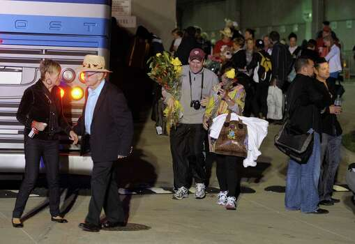 Passengers of the Carnival Triumph walk to their buses after docking at the cruise terminal in Mobile, Ala., Thursday, Feb. 14, 2013. The passengers will be bused to New Orleans for the night. The ship with more than 4,200 passengers and crew members has been idled for nearly a week in the Gulf of Mexico following an engine room fire. (AP Photo/G M Andrews) Photo: G M Andrews, Associated Press / FR35697 AP
