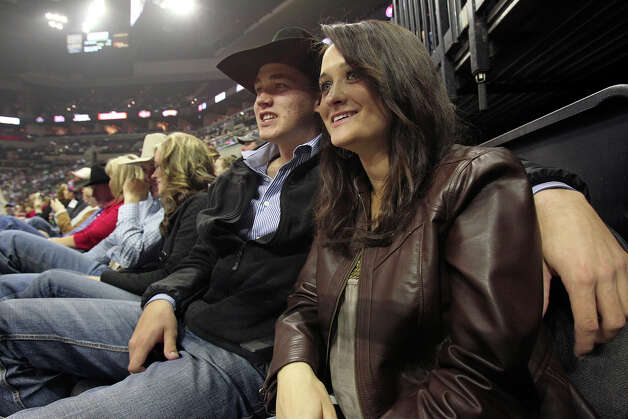 Rozlyn Reeves and Byron Oxford watch rodeo action from the chute area on Valentines Day in the AT&T Center.  The rodeo hosted a  Dust and Bubbles event for Valentines Day with champagne and food in a special suite for rodeo watchers, but plenty of sweethearts like these two could be seen out in the arena on February 14, 2013. Photo: Tom Reel