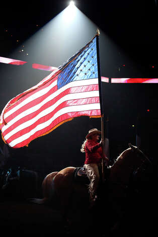 The U.S. flag is brought into the arena before action begins as the rodeo hosts the Dust and Bubbles event for Valentines Day with champagne and food in a special suite for rodeo watchers on February 14, 2013. Photo: Tom Reel