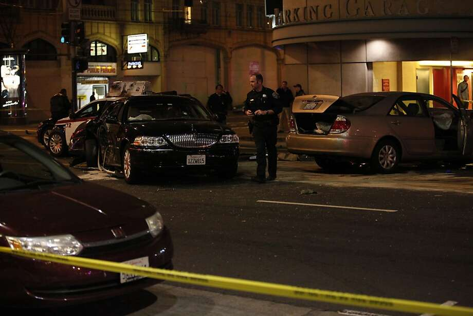 Police officers investigate the scene of a four-car crash at Fifth and Mission streets after a car-theft suspect fleeing authorities smashed into a vehicle, which hit two other cars. Photo: Nicole FrugŽ, The Chronicle