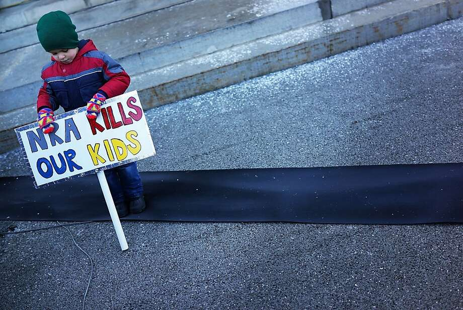 "Connor Garrett, 5, holds a sign during a rally at the Connecticut State Capital to promote gun control legislation in the wake of the December 14, 2012, school shooting in Newtown on February 14, 2013 in Hartford, Connecticut. Referred to as the ""March for Change"" and held on the two-month anniversary of the massacre in Newtown, Connecticut, participants called for improved gun safety laws. Among the safety measures being demanded are for universal background checks, more work within the mental health community and restricting high-capacity magazines. Photo: Spencer Platt, Getty Images"