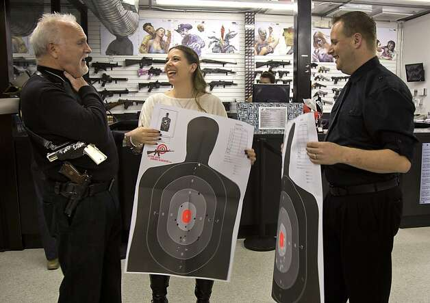 "Rev. ""Jimmy Mac"" McNamara, also known as the Pistol Packing Preacher, talks with Tanya, center, and Ted Morris, right, after the two took their wedding vows from him and then fired guns on the shooting range at the Guns and Ammo Garage, Thursday, Feb. 14, 2013, in Las Vegas.   The shooting range and gun store offered free vow renewals and wedding ceremonies by McNamara throughout the day on Thursday. Photo: Julie Jacobson, Associated Press"