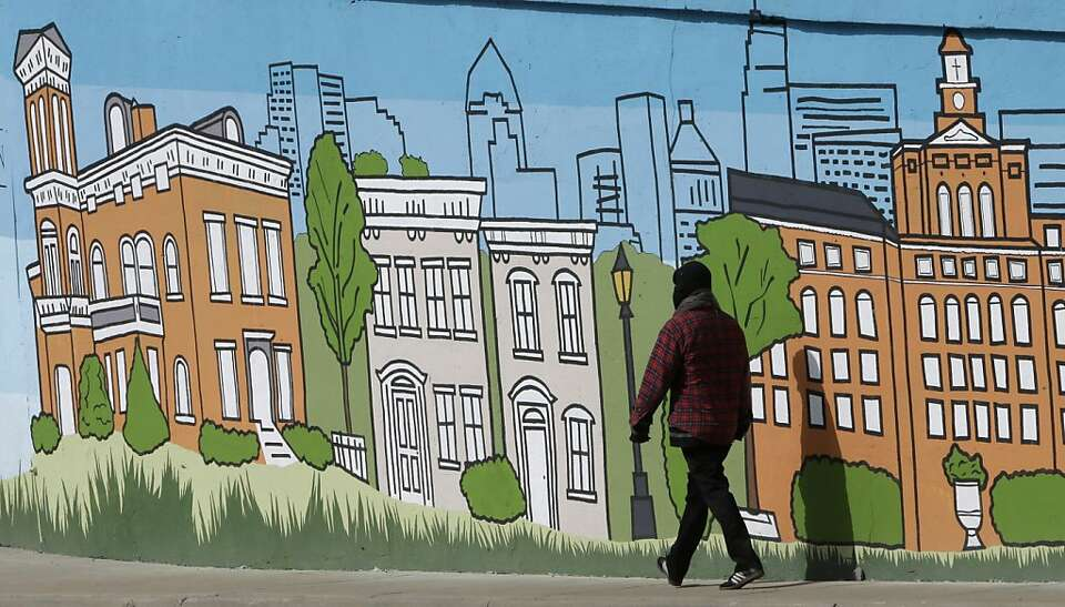A pedestrian walks past a mural showing the skyline and several landmark buildings of Cincinnati, Th