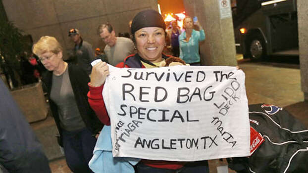 Veronica Arriaga, of Angleton, Texas, a passenger from the disabled Carnival Triumph cruise ship, holds a sign referring to the red biohazard bags used as toilets, after arriving by bus at the Hilton Riverside Hotel in New Orleans, Friday, Feb. 15, 2013. The ship had been idled for nearly a week in the Gulf of Mexico following an engine room fire. Photo: Gerald Herbert, . / AP