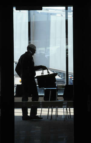 A passenger waits for the airplane at the Jack Brooks Regional Airport on Thursday.  Photo taken Thursday, February 14, 2013 Guiseppe Barranco/The Enterprise Photo: Guiseppe Barranco, STAFF PHOTOGRAPHER / The Beaumont Enterprise