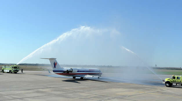 As part of a tradition, airport fire trucks spray water over American Airline's inaugural flight out of the Jack Brooks Regional Airport on Thursday. The company made its first flight to Dallas.  Photo taken Thursday, February 14, 2013 Guiseppe Barranco/The Enterprise Photo: Guiseppe Barranco, STAFF PHOTOGRAPHER / The Beaumont Enterprise