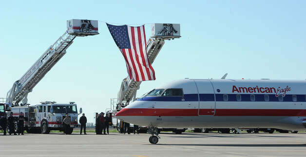 American Airlines plane is met on the tarmac with flags and fanfare at the Jack Brooks Regional Airport runway on Thursday. Photo taken Thursday, February 14, 2013 Guiseppe Barranco/The Enterprise Photo: Guiseppe Barranco, STAFF PHOTOGRAPHER / The Beaumont Enterprise