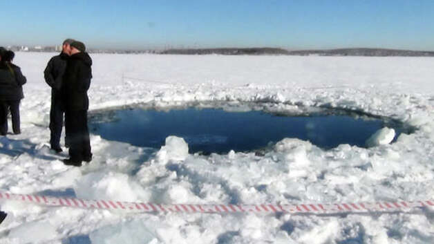 "A handout photo taken on February 15, 2013, and provided by Chelyabinsk region police department shows people standing near a six-metre (20-foot) hole in the ice of a frozen lake, reportedly the site of a meteor fall, outside the town of Chebakul in the Chelyabinsk region. A plunging meteor exploded today with a blinding flash above central Russia, setting off a shock wave that shattered windows and hurt over 500 people in an event unprecedented in modern times. The office of the local governor said in a statement that a meteorite had fallen into a lake outside the town of Chebakul in the Chelyabinsk region. AFP PHOTO / CHELYABINSK REGION POLICE DEPARTMENT -- RESTRICTED TO EDITORIAL USE - MANDATORY CREDIT ""AFP PHOTO /  CHELYABINSK REGION POLICE DEPARTMENT"" - NO MARKETING NO ADVERTISING CAMPAIGNS - DISTRIBUTED AS A SERVICE TO CLIENTS ---/AFP/Getty Images Photo: -, . / AFP"