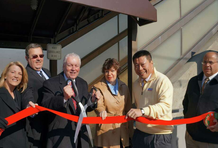 Local officails, from left state Rep. Brenda Kupchick, R-Fairfield, Parking Authority Chairman Ronald Pine, First Selectman Mike Tetreau, Parking Authoirty Manager Cindy Placko, state Rep. Tony Hwang, R-Fairfield and Public Works Director Joseph Michelangelo, cut the red ribbon marking the official opening of the canopied stairwells at the downtown train station Friday. Photo: Genevieve Reilly / Fairfield Citizen