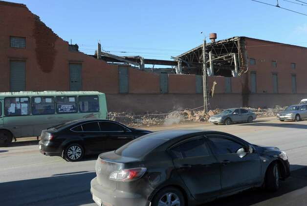 Cars pass by a zinc factory building with it's roof collapsed in Chelyabinsk, about 1500 kilometers (930 miles) east of Moscow, Friday, Feb. 15, 2013. There was no immediate clarification of whether the collapse was caused by meteorites or by a shock wave from one of the explosions. A meteor that scientists estimate weighed 10 tons (11 tons) streaked at supersonic speed over Russia's Ural Mountains on Friday, setting off blasts that injured some 500 people and frightened countless more. (AP Photo/Boris Kaulin) Photo: Associated Press