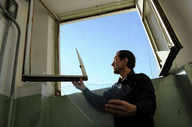 A local resident repairs a window broken by a shock wave from a meteor explosion in Chelyabinsk, about 1500 kilometers (930 miles) east of Moscow,  Friday, Feb. 15, 2013. A meteor that scientists estimate weighed 10 tons (11 tons) streaked at supersonic speed over Russia's Ural Mountains on Friday, setting off blasts that injured some 500 people and frightened countless more. (AP Photo/Boris Kaulin) Photo: Associated Press