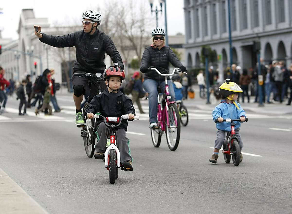A family rides by the Ferry Building and enjoys the annual Sunday Streets neighborhood street fairs on Sunday, March 11, 2012. Automotive traffic on Embarcadero Street from Howard Street down to the Fisherman's Wharf was closed for runners, bicyclists, and anyone else to enjoy. The first Sunday Streets of 2013 starts next month.