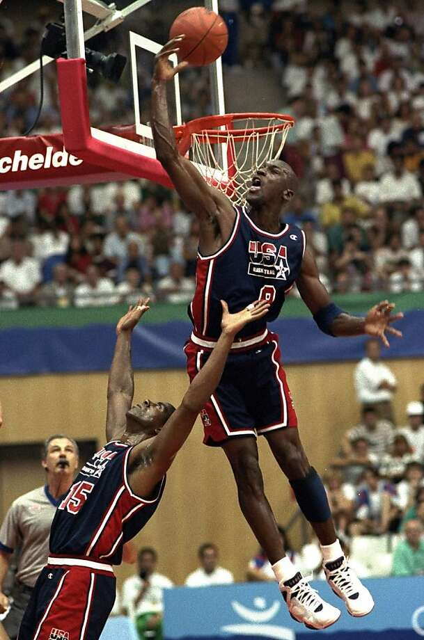 In this July 27, 1992 file photo, USA's Michael Jordan sails high above teammate Magic Johnson knocking away a shot during the first half of their preliminary round basketball game with Croatia at the Summer Olympics in Barcelona.  Photo: Susan Ragan, Associated Press