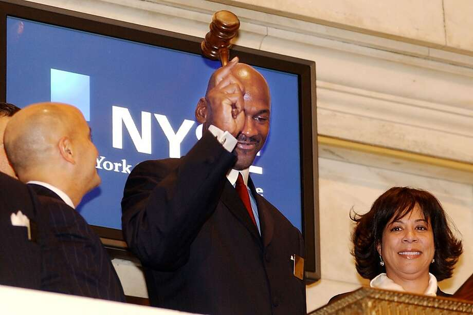Michael Jordan bangs the gavel after ringing the closing bell at the New York Stock Exchange in 2001.  With Jordan are NYSE Chairman Richard Grasso and Jordan's then-wife Juanita. The couple divorced in 2006. Photo: Richard Drew, Associated Press