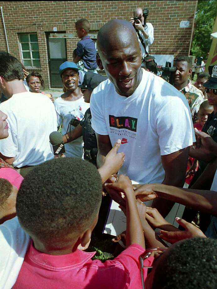 Jordan shakes hands with young fans after dedicating a new basketball court made from 25,000 recycled Nike shoes at the LeMoyne Gardens Public Housing Development in Memphis in 1994. Photo: Kent Phillips, Associated Press