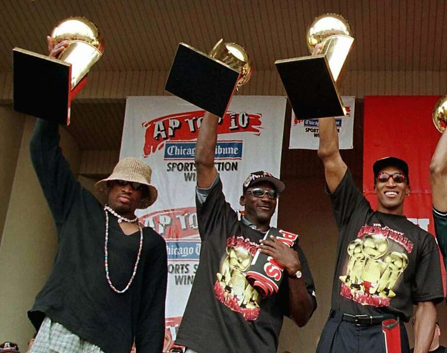 Chicago Bulls Dennis Rodman, Michael Jordan and Scottie Pippen hold up their NBA Championship trophies at a victory rally on June 16, 1997.  Photo: Sue Ogrocki, REUTERS