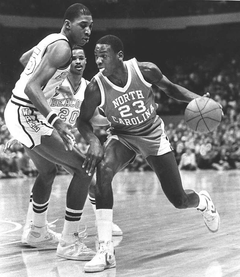 North Carolina's Michael Jordan drives around Wake Forest's Anthony Teachey, left, and Danny Young (20) in this Feb. 17, 1982 photo at the Greensboro Coliseum in Greensboro, N.C.  Photo: Bob Jordan, Associated Press