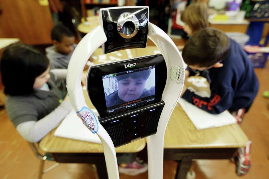 In this Thursday, Jan. 24, 2013 photo, Devon Carrow attends Winchester Elementary School from home while operating a robot in the classroom, in West Seneca N.Y. Carrow's life-threatening allergies don't allow him to go to school. But the 4-foot-tall robot with a wireless video hookup gives him the school experience remotely, allowing him to participate in class, stroll through the hallways, hang out at recess and even take to the auditorium stage when there's a show. (AP Photo/David Duprey) Photo: David Duprey