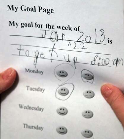 In this Tuesday, Jan. 22, 2013 photo, Devon Carrow looks at his weekly goals while attending school from home while operating a robot in the classroom, in Orchard Park N.Y. Carrow's life-threatening allergies don't allow him to go to school. But the 4-foot-tall robot with a wireless video hookup gives him the school experience remotely, allowing him to participate in class, stroll through the hallways, hang out at recess and even take to the auditorium stage when there's a show.  (AP Photo/David Duprey) Photo: David Duprey