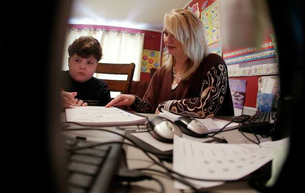 In this Tuesday, Jan. 22, 2013 photo, Devon Carrow works with teacher Sheri Voss while attending school from home while operating a robot in the classroom, in Orchard Park N.Y. Carrow's life-threatening allergies don't allow him to go to school. But the 4-foot-tall robot with a wireless video hookup gives him the school experience remotely, allowing him to participate in class, stroll through the hallways, hang out at recess and even take to the auditorium stage when there's a show.  (AP Photo/David Duprey) Photo: David Duprey