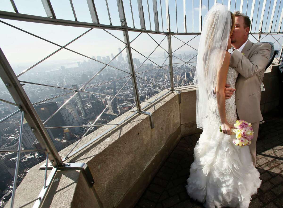 """Newlyweds Danielle Brabham, 39, and Michael Lynch, 41, from Miami Shores, Fla., kiss while posing for pictures on the Empire State Building viewing platform after their Valentine's Day wedding on Thursday, Feb. 14, 2013 in New York. Brabham and Lynch were among three couples chosen for the 19th Annual Weddings Event, """"Love is in the Air,"""" designed by celebrity designer Preston Bailey, after submitting their personal love stories to the Empire State Building's Facebook page."""