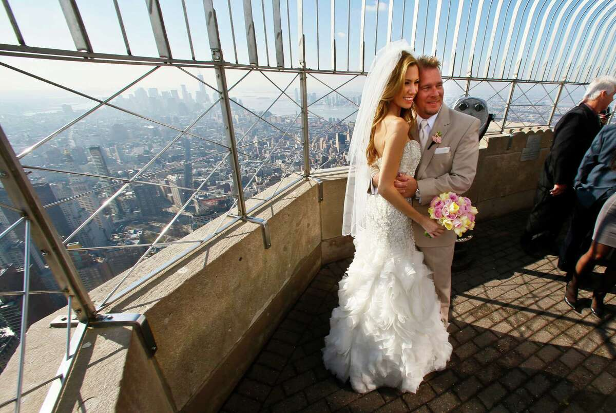 """Newlyweds Danielle Brabham, 39, and Michael Lynch, 41, from Miami Shores, Fla., pose for pictures at the Empire State Building viewing platform after their Valentine's Day wedding on Thursday, Feb. 14, 2013 in New York. Brabham and Lynch were among three couples chosen for the 19th Annual Weddings Event, """"Love is in the Air,"""" designed by celebrity designer Preston Bailey, after submitting their personal love stories to the Empire State Building's Facebook page."""
