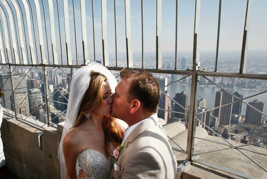 "Newlyweds Danielle Brabham, 39, and Michael Lynch, 41, from Miami Shores, Fla., kiss  while posing for pictures on the Empire State Building viewing platform after their Valentine's Day wedding on Thursday, Feb. 14, 2013 in New York.  Brabham and Lynch were among three couples chosen for the 19th Annual Weddings Event, ""Love is in the Air,"" designed by celebrity designer Preston Bailey, after submitting their personal love stories to the  Empire State Building's Facebook page. Photo: Bebeto Matthews, AP / AP"
