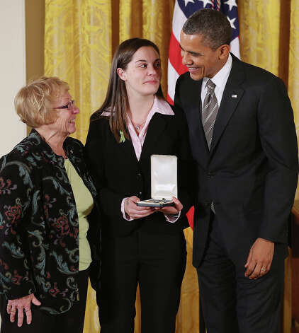 "President Barack Obama presents Erica and Cheryl Lafferty with the 2012 Presidential Citizens Medal, the nation's second-highest civilian honor, on behalf of their mother and daughter Dawn Lafferty Hochsprung in the East Room of the White House February 15, 2013 in Washington, DC. Principal Dawn Lafferty Hochsprung was killed during a mass shooting that left 26 people dead at Sandy Hook Elementary School in December 2012. ""Their selflessness and courage inspire us all to look for opportunities to better serve our communities and our country,"" Obama said about this year's recipients. Photo: Chip Somodevilla, Getty Images / 2013 Getty Images"