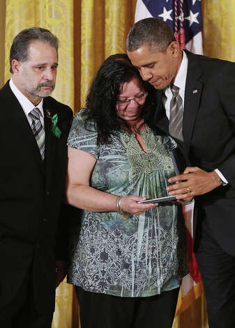 "President Barack Obama presents Donna and Carlos Soto Sr. with the 2012 Presidential Citizens Medal, the nation's second-highest civilian honor, on behalf of their daughter Victoria Soto in the East Room of the White House February 15, 2013 in Washington, DC. First grad teacher, Victoria Soto was killed during a mass shooting that left 26 people dead at Sandy Hook Elementary School in December 2012. ""Their selflessness and courage inspire us all to look for opportunities to better serve our communities and our country,"" Obama said about this year's recipients. Photo: Chip Somodevilla, Getty Images / 2013 Getty Images"