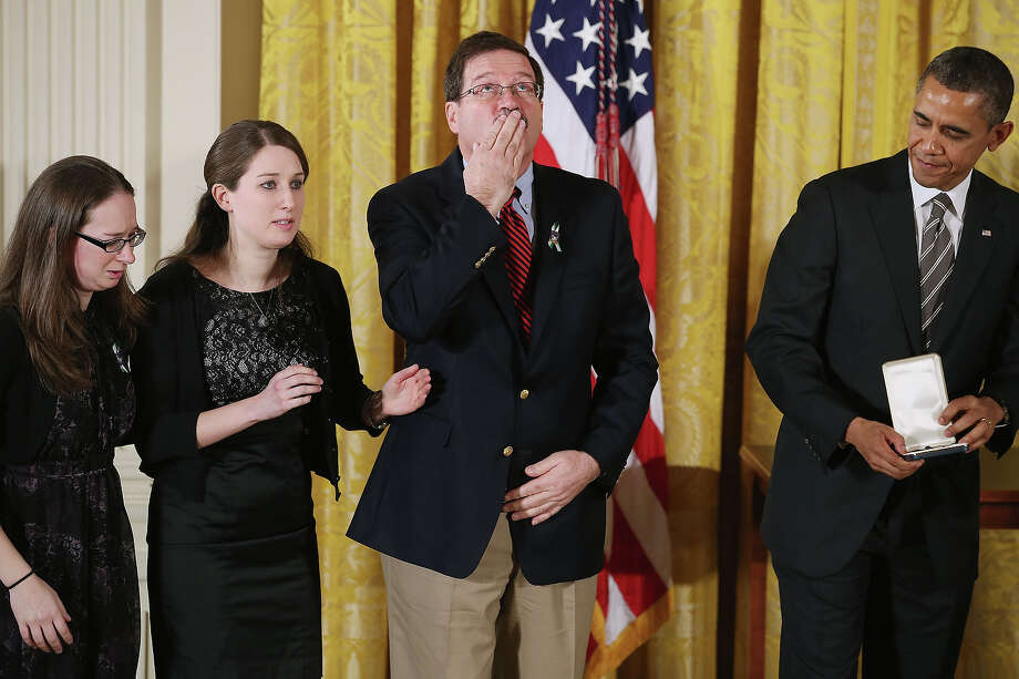 "Bill Sherlach blows a kiss skyward as President Barack Obama presents him and daughters Katy Sherlach and Maura Lynn Schwartz with the 2012 Presidential Citizens Medal, the nation's second-highest civilian honor, on behalf of their wife and mother Mary Sherlach in the East Room of the White House February 15, 2013 in Washington, DC. School psychologist Mary Sherlach was killed during a mass shooting that left 26 people dead at Sandy Hook Elementary School in December 2012. ""Their selflessness and courage inspire us all to look for opportunities to better serve our communities and our country,"" Obama said about this year's recipients. Photo: Chip Somodevilla, Getty Images / 2013 Getty Images"
