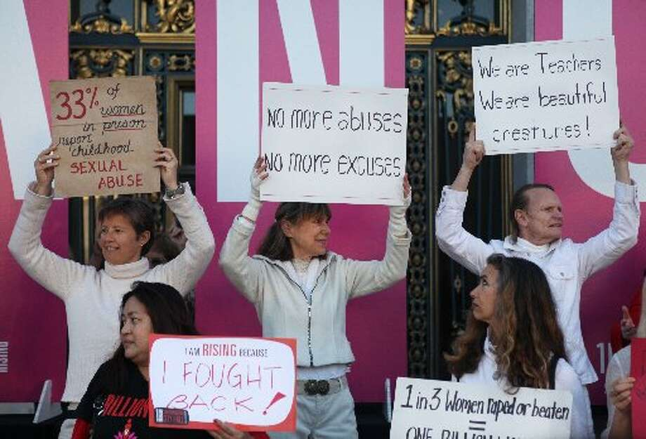 Women show their support for the event and hold signs, some of which detail grim statistics.
