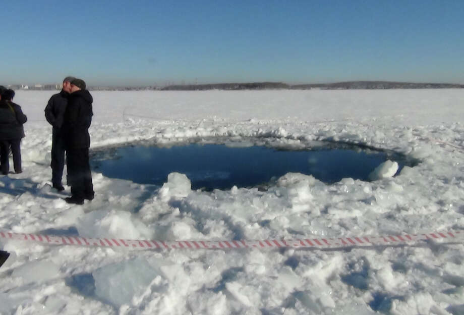 A circular hole in the ice of Chebarkul Lake where a meteor reportedly struck the lake near Chelyabinsk, about 930 miles east of Moscow,  Russia,  Friday. (AP Photo) Photo: Associated Press