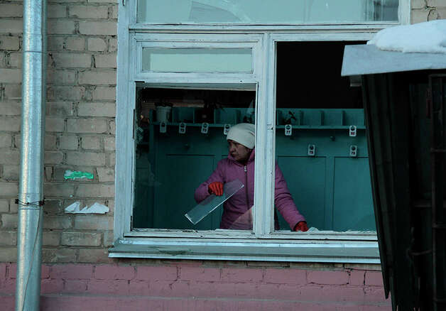 In this photo provided by Chelyabinsk.ru a woman cleans away glass debris from a window after a meteorite explosion over Chelyabinsk region on Friday, Feb. 15, 2013. A meteor exploded in the sky above Russia on Friday, causing a shockwave that blew out windows injuring hundreds of people and sending fragments falling to the ground in the Ural Mountains.  The Russian Academy of Sciences said in a statement hours after the Friday morning fall that the meteor entered the Earth's atmosphere at a speed of at least 54,000 kph (33,000 mph) and shattered about 30-50 kilometers (18-32 miles) above ground. The fall caused explosions that broke glass over a wide area. (AP Photo/ Yevgenia Yemelyanova, Chelyabinsk.ru) Photo: Associated Press
