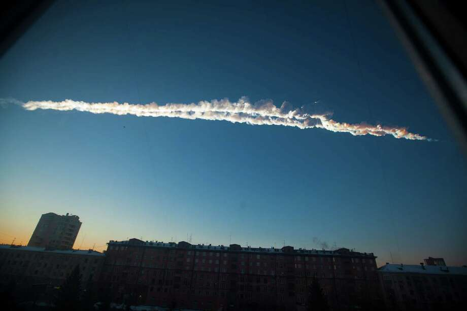 In this photo provided by Chelyabinsk.ru a meteorite contrail is seen over Chelyabinsk on Friday. A meteor streaked across the sky of Russia's Ural Mountains on Friday morning, causing sharp explosions and reportedly injuring more than 1,100, including many hurt by broken glass. (AP Photo/Chelyabinsk.ru) Photo: Associated Press