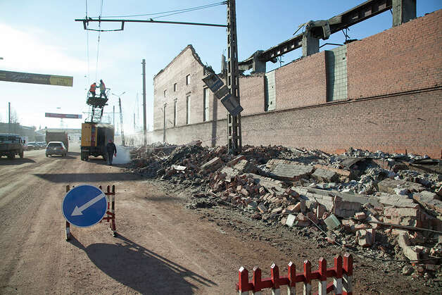 In this photo provided by Chelyabinsk.ru municipal workers repair damaged electric power circuit outside a zinc factory building with about 600 square meters (6000 square feet) of a roof collapsed  after a meteorite exploded over in Chelyabinsk region on Friday, Feb. 15, 2013 A meteor streaked across the sky of Russia�s Ural Mountains on Friday morning, causing sharp explosions and reportedly injuring around 100 people, including many hurt by broken glass. (AP Photo/ Oleg Kargapolov, Chelyabinsk.ru) Photo: Associated Press