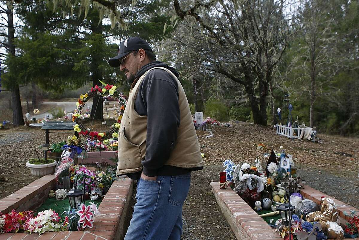 Trent Campbell talks about his son at the gravesite of his wife (left) and son (right) at the Cahto reservation cemetery in Laytonville, Calif., on Monday, January 28, 2013. His wife passed away suddenly of a brief illness on July 29, 2009, and their nineteen year old son was at his mom's gravesite on October 11, 2009 when he took his life with a gun he had gotten in trade for a puppy.