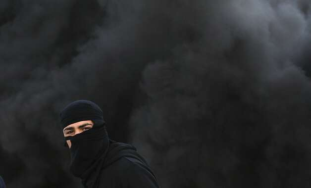 A masked Palestinian clashes with Israeli soldiers (off camera) during a rally in Jenin, West Bank, in support of Palestinian prisoners waging a hunger strike. Photo: Mohammed Ballas, Associated Press