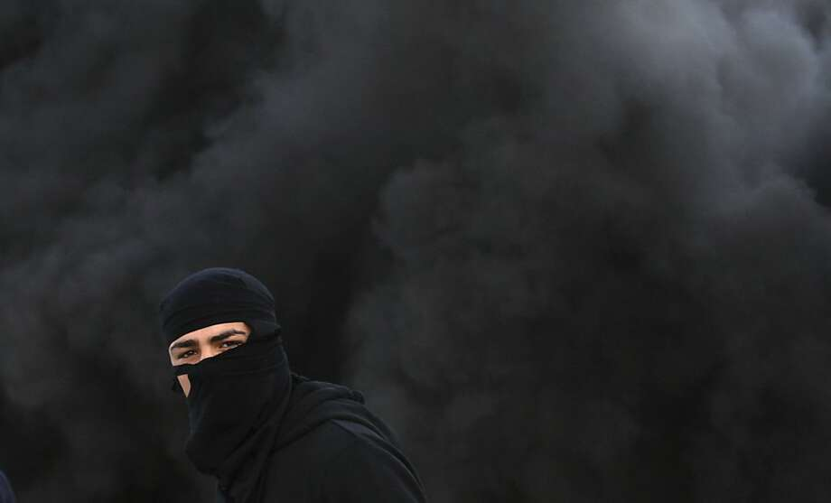 A Palestinian wears a mask during clashes with the Israeli army north of the West Bank city of Jenin in support to the Palestinian prisoners on hunger strike in Israeli jails and against the administrative detention, Friday, Feb. 15, 2013. Photo: Mohammed Ballas, Associated Press