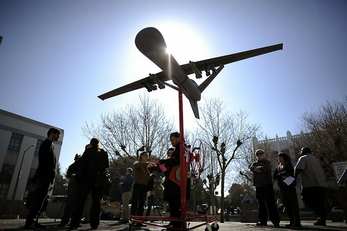 Drone opponents gather and hand out fliers under a mock-up of a military style