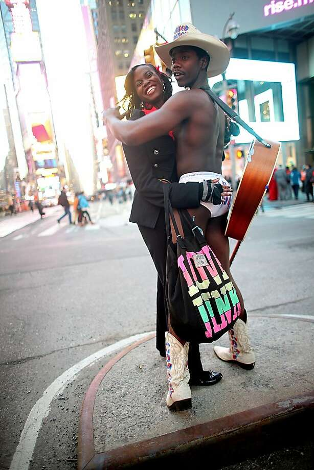 "Always beware of pickpockets in Times Square: Mora Giwa frisks ""Naked Cowboy"" Titus Gandy's saddlebags during Valentine's Day celebrations in New York's Times Square. Photo: Mario Tama, Getty Images"