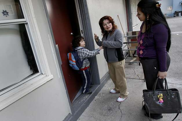 Jose (left) and his mother Rosalba prepare to enter their apartment as case provider Karla Ramos (right) speaks with them. Rosalba Penaloza and her two children live in Potrero Terrace, one of the most notorious public housing sites in San Francisco, Calif.  She has been on an emergency transfer list for nine months but is still stuck.  Her case provider, Karla Ramos, is trying to help her into a new home. Photo: Brant Ward, The Chronicle
