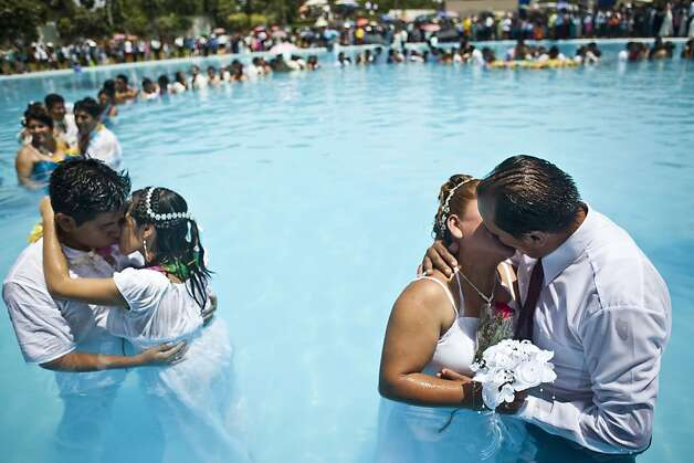 It's a good day for a wet wedding? Couples kiss after taking their vows inside a public pool in Lima during a Valentine's Day marriage ceremony whose logic escapes us. Photo: Ernesto Benavides, AFP/Getty Images