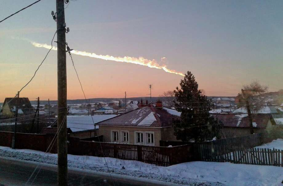 In this photo provided by E1.ru a meteorite contrail is seen over a vilage of Bolshoe Sidelnikovo 50 km of Chelyabinsk on Friday, Feb. 15, 2013. A meteor streaked across the sky of Russia�s Ural Mountains on Friday morning, causing sharp explosions and reportedly injuring around 100 people, including many hurt by broken glass. (AP Photo/ Nadezhda Luchinina, E1.ru) Photo: Associated Press