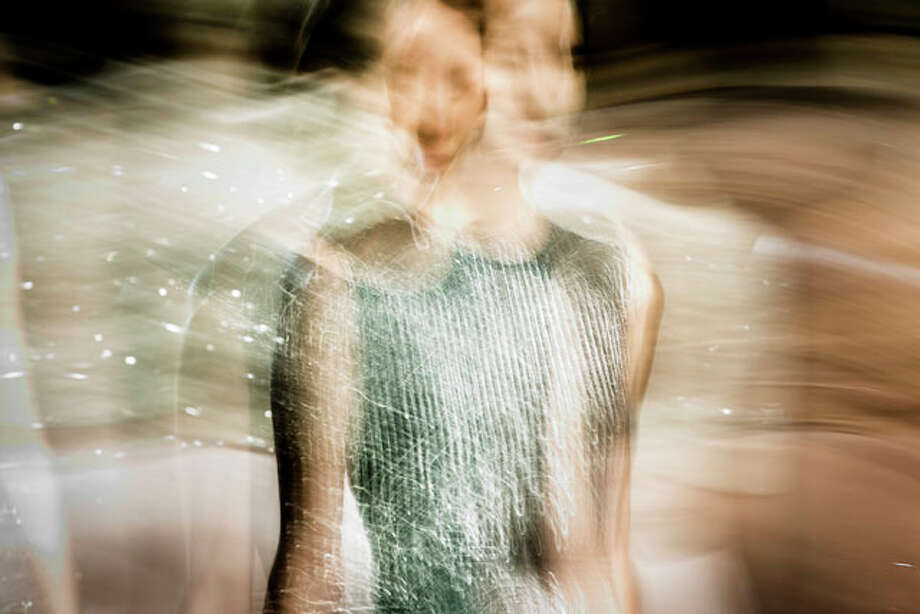 In this photo made with a long exposure, a model walks the runway at the Jenny Packham Fall 2013 fashion show during Fashion Week, Tuesday, Feb. 12, 2013, in New York. (AP Photo/John Minchillo) Photo: John Minchillo, Express-News / FR170537 AP