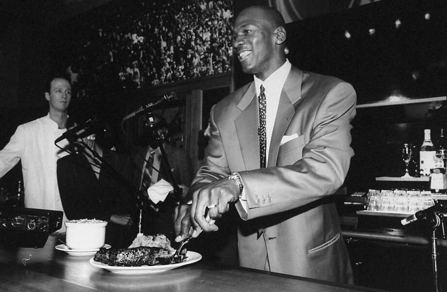 MJ samples steak and potatoes at the opening of his Michael Jordan's restaurant. Photo: Steve Kagan, Getty Images
