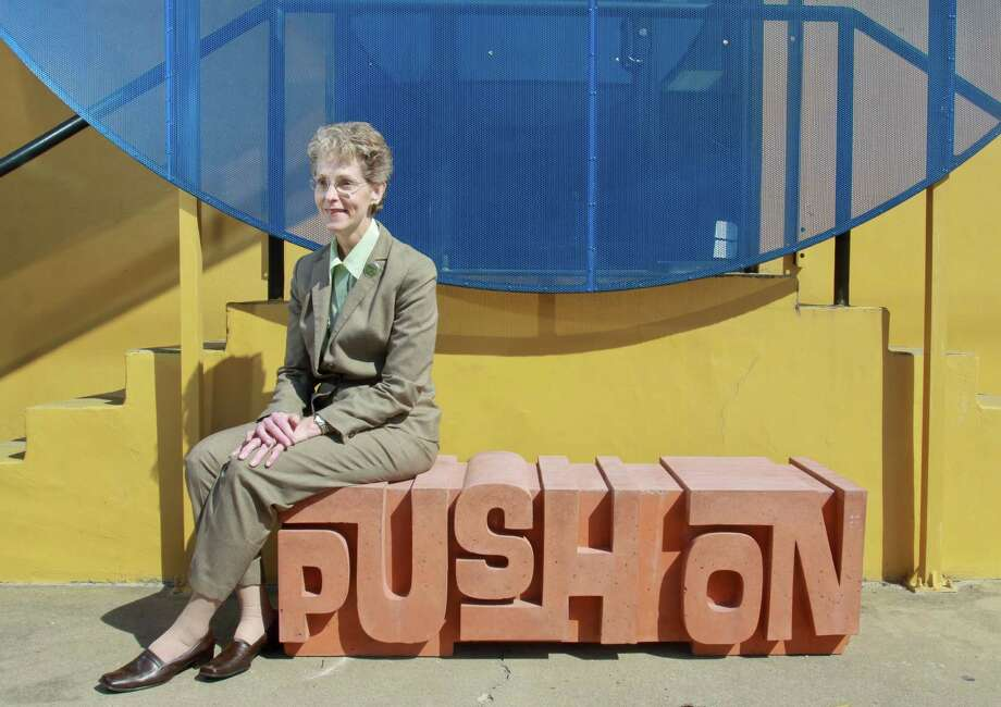 "Diane Schenke, president of the Greater East End Management District, sits on a prototype ""functional art"" bench designed by artist Anthony Shumate in front of her office. Photo: Gary Fountain, Freelance / Copyright 2013 Gary Fountain."