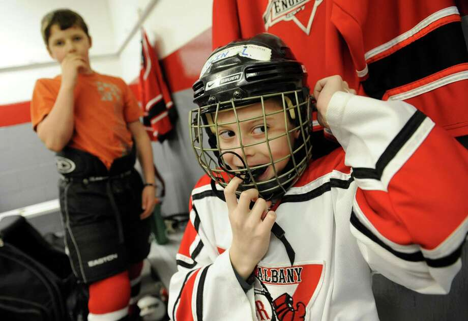 Troy Albany Junior Engineers hockey player Collin Lagios, 11, of Guilderland puts on his helmet before playing the Yale Bulldogs of Conn. at the 20th annual ?Rink Rat? youth hockey tournament on Friday Feb. 15, 2013 in Troy, N.Y. Sam Besch, 11, of West Sand Lake continues to get suited up. The tournament consist of teams from 7 states, and 2 provinces including teams from Ottawa, Pittsburgh, Boston, Montreal, Quebec, and Princeton. Events are held at area ice rinks throughout the Capital Region. (Lori Van Buren / Times Union) Photo: Lori Van Buren