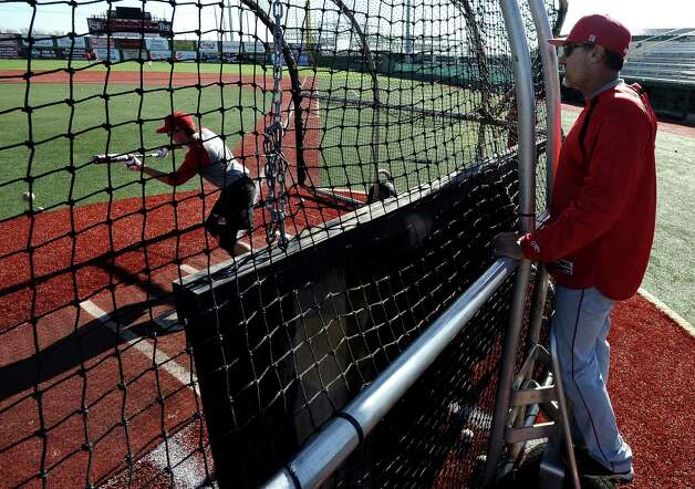 Scott Hatten, right, looks over batting practice while Jude Vidrine, left, lays a bunt during Lamar University baseball practice at Vincent-Beck Stadium on Thursday, February 14, 2013. Photo taken: Randy Edwards/The Enterprise